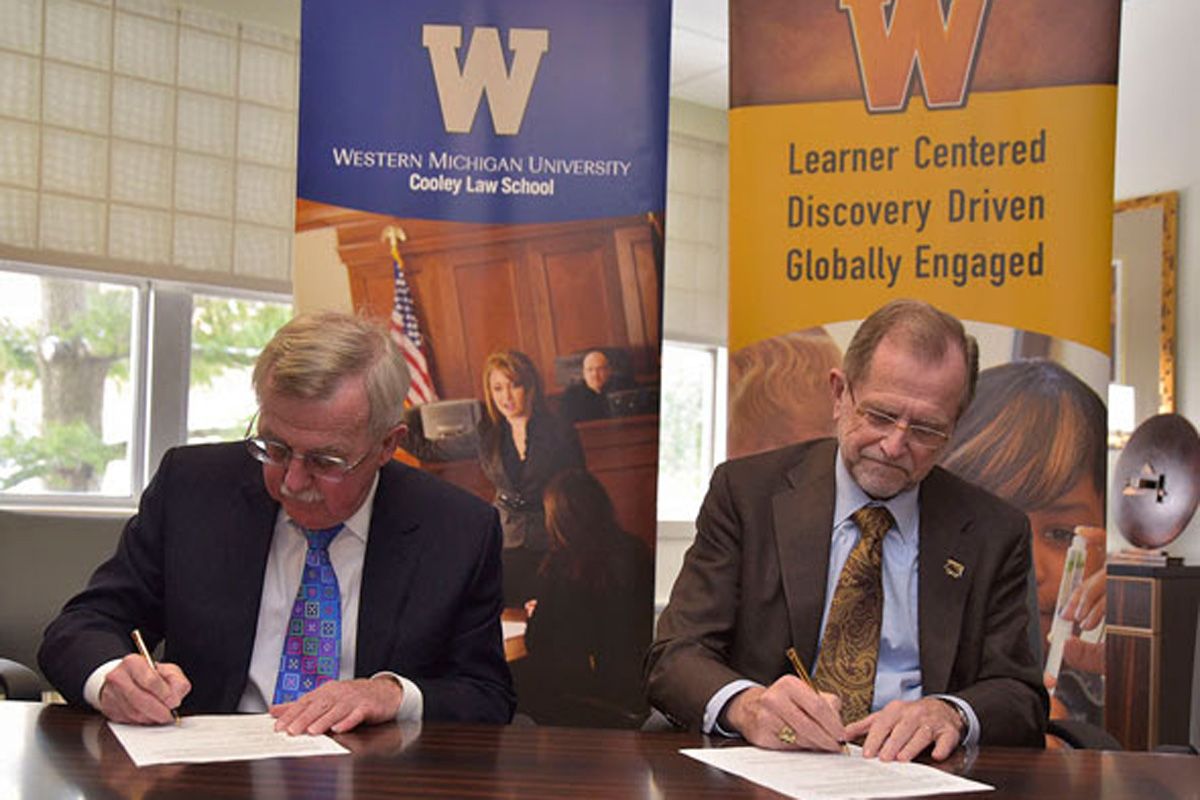 WMU-Cooley President Don LeDuc and WMU President John Dunn sign partnership agreements